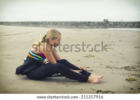 Teen girl putting on a wetsuit sitting on the beach at Rockaway Oregon - stock photo