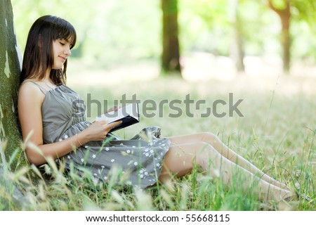teen girl reading book  leant against tree in park - stock photo