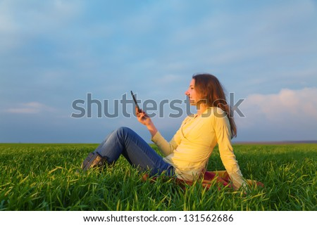 Teen girl reading electronic book outdoors at summer time - stock photo