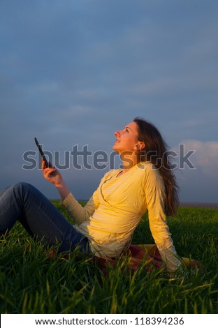 Teen girl reading electronic book sitting outdoors - stock photo