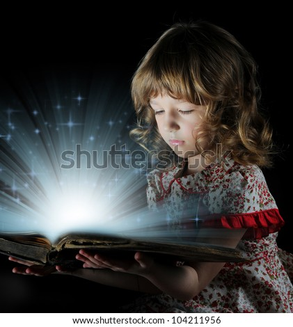 Teen girl reading the book on a black background - stock photo