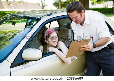 Teen girl reviews her score on the driving test with the instructor. - stock photo