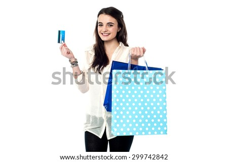 Teen girl showing credit card after her shopping - stock photo