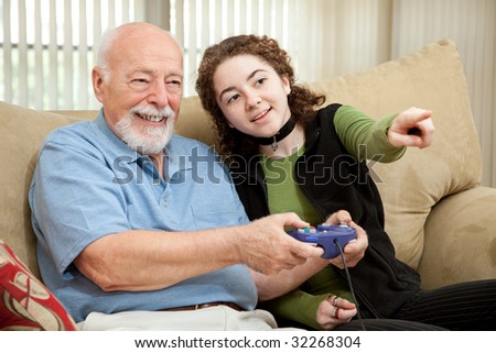 Teen girl shows her grandfather how to play video games. - stock photo