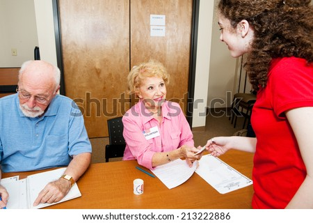 Teen girl shows her voter ID and picks up her ballot at the polling station.   - stock photo