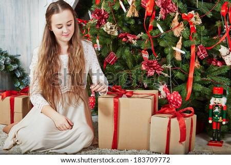 Teen girl sits on furry rug under Christmas tree among cardboard gift boxes - stock photo