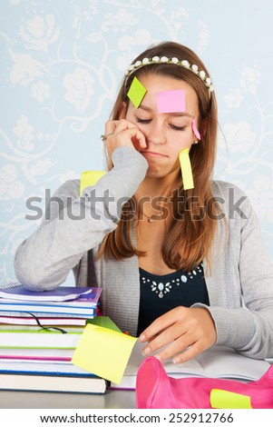 Teen girl sitting at desk with homework for school and having a lot to remember - stock photo