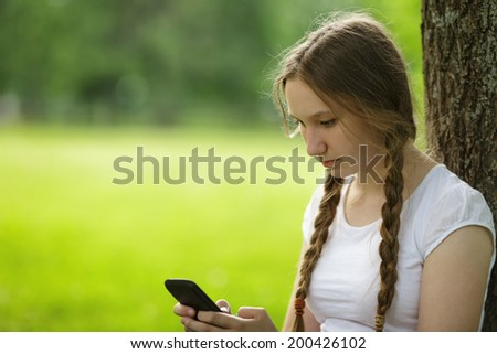 teen girl sitting near tree with mobile phone outdoors in park