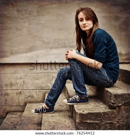 Teen girl sitting on stairs against grunge wall - stock photo