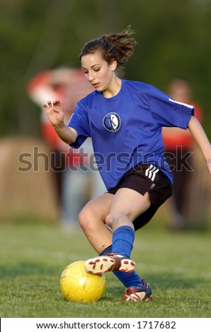 Teen girl soccer player makes a move with a yellow soccer ball - stock photo