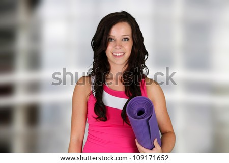 Teen girl standing with her yoga mat at the gym - stock photo