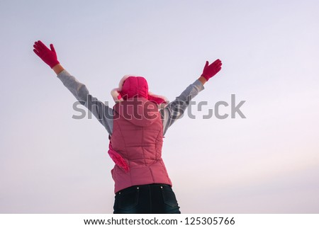 Teen girl staying with raised hands against blue sky - stock photo