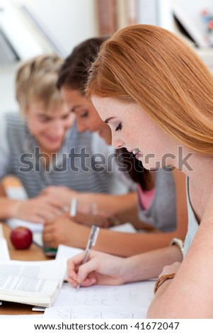 Teen girl studying in the library with her friends. Concept of education - stock photo