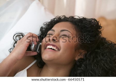 Teen girl talking on mobile phone from bed - stock photo