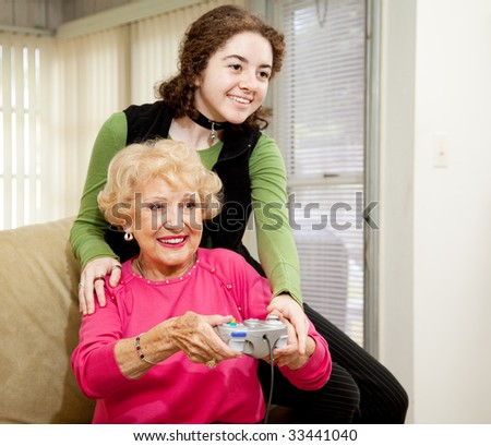 Teen girl teaching her grandmother how to play video games.  Fun family moment. - stock photo