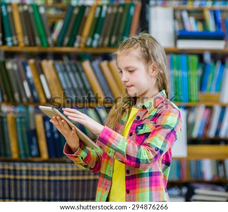 Teen girl using a tablet computer in a library - stock photo