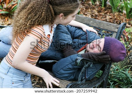Teen girl volunteers to help homeless man in the park.  Or daughter helping father. - stock photo