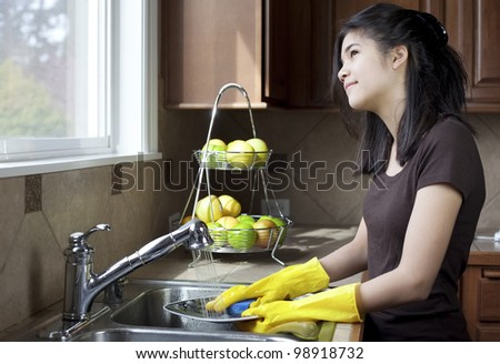 Teen girl washing dishes at kitchen sink, daydreaming or looking out the window with thoughtful expression. - stock photo