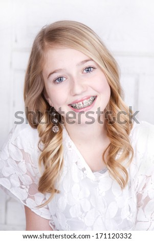 Teen girl wearing braces wearing white - stock photo
