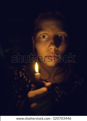 Teen girl with a candle, fear on her face - stock photo