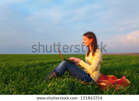 Teen girl with a laptop sitting at field - stock photo