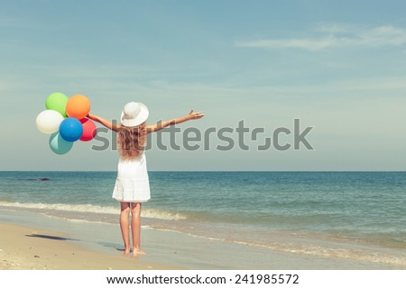 Teen girl with balloons standing on the beach at the day time - stock photo