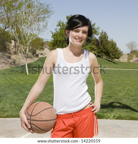 Teen girl with basketball hangs out at a park
