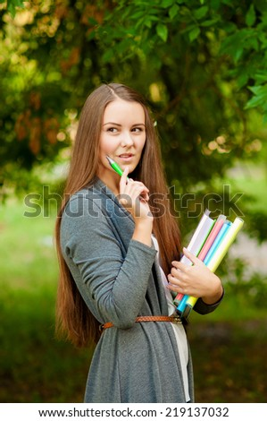 Teen girl with books in hands near tree - stock photo