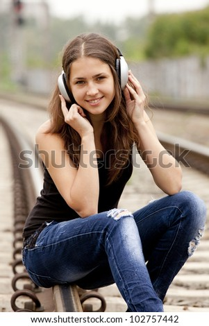 Teen girl with headphones at railways. - stock photo