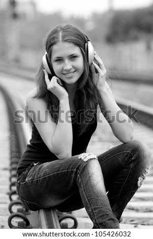 Teen girl with headphones at railways. Photo in black and white style. - stock photo
