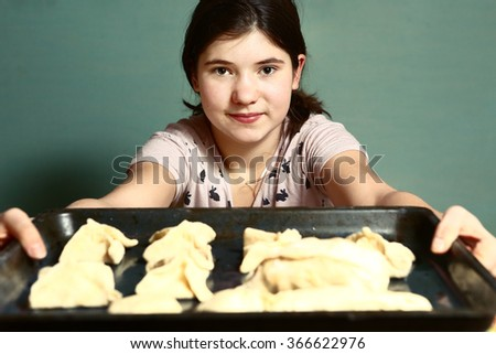teen girl with long dark hair cooking bake pies show them on the pan tray before put into oven - stock photo