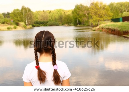 teen girl with plait back close up portrait on the summer lake nature background - stock photo