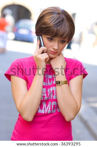 teen girl with sad expression talking to mobile phone - stock photo