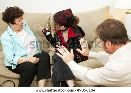 Teen girl yelling at her mother during a family counseling session. - stock photo
