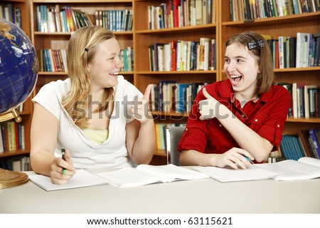 Teen girls doing their homework in the school library and giving each other the thumbs-up sign. - stock photo