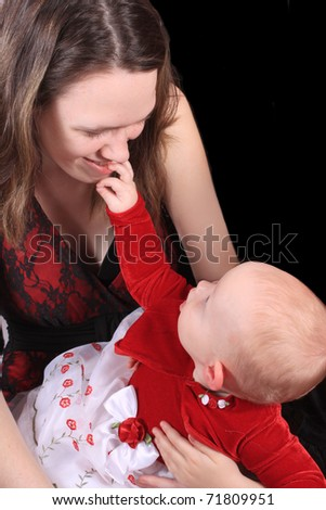 Teen girls holds baby as she grabs for her face in wonderment