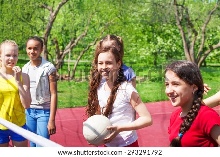 Teen girls playing volleyball together on ground - stock photo