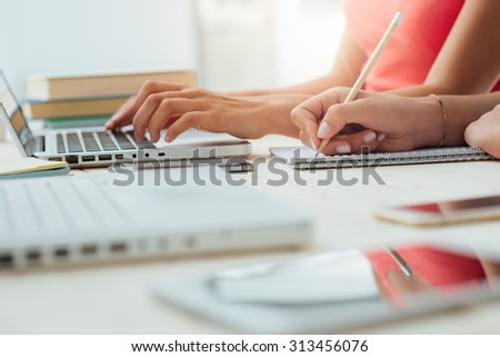 Teen girls studying at desk and doing homeworks, one is using a laptop and the other one is writing on a notebook, education concept, unrecognizable people