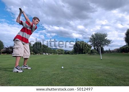 Teen golfer tees off - stock photo
