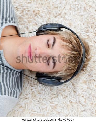 Teen guy listening to music with headphones - stock photo