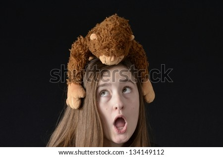 Teen looking up at stuffed monkey on her head with surprised expression - stock photo