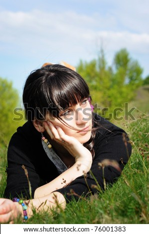 Teen lying on grass thinking - stock photo