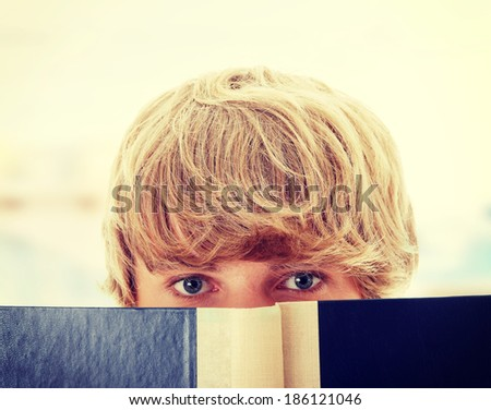 Teen man reading book - stock photo
