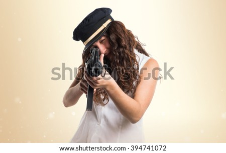 Teen model wearing sea hat holding a rifle - stock photo