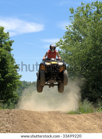 teen on a fourwheeler getting some air - stock photo