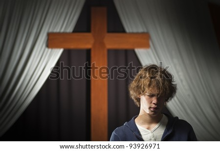 Teen prays in front of a cross - stock photo