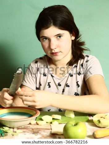 teen pretty girl with long dark hairs prepare pies with cut apples - stock photo