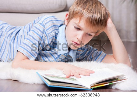 Teen reading a book in the room. - stock photo