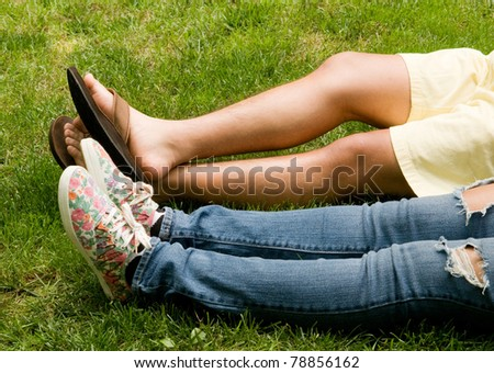 Teen romance - legs of boy and girl in the grass - stock photo