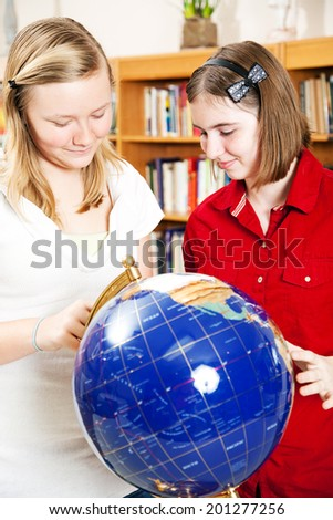 Teen school girls using a globe for research in the library.   - stock photo